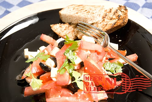 Zomerse salade van Roma-trostomaat, zwarte olijven, mozzarella en verse koriander