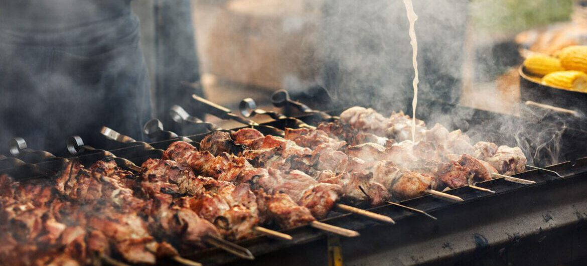 Delicious bbq kebab grilling on open grill, outdoor kitchen