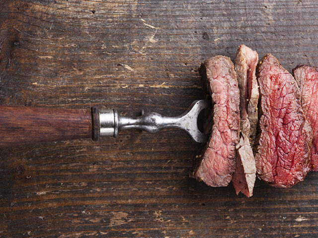 Plakjes beef steak biefstuk tournedos ossenhaas op vleesvork op houten achtergrond meerdanvlees Slices of beef steak on meat fork on wooden background